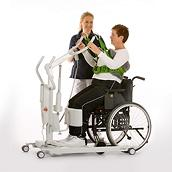 A clinician helps a female patient stand from a wheelchair using a SupportVest Lift Aid