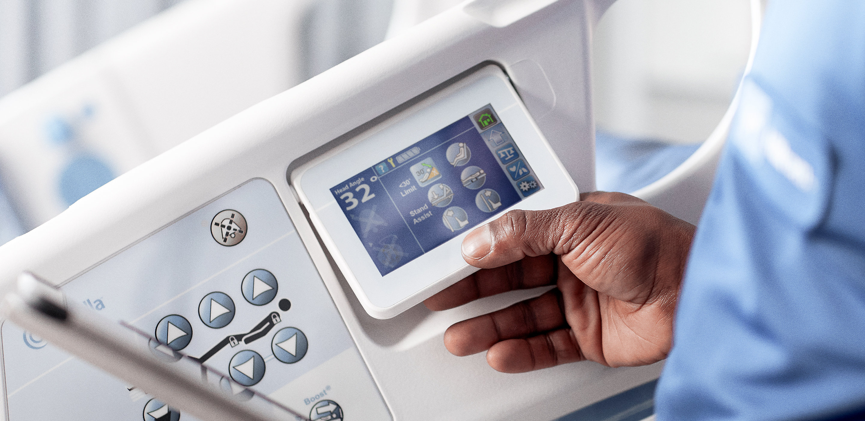 Un technicien de Hillrom tient une tablette pendant l'inspection d'un lit Centrella<sup>®</sup> Smart+.