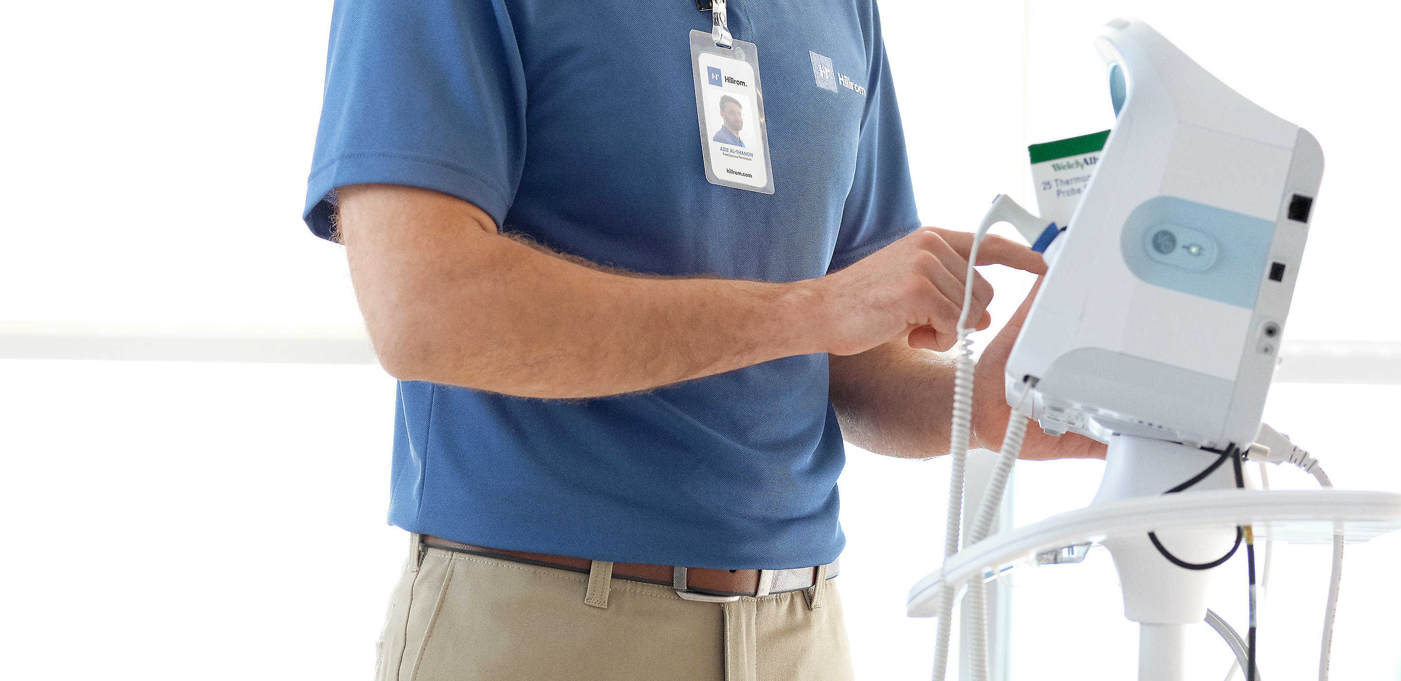 A Hillrom service technician works on a Connex® Vital Signs Monitor in a hospital room. A Centrella® Smart+ Bed is also visible.
