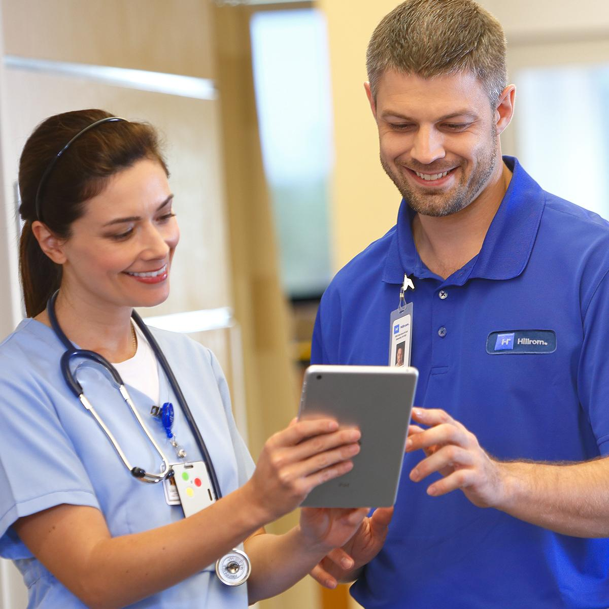 A care provider and a Hillrom support professional consult in a corridor. The clinician shows him data from her tablet device.