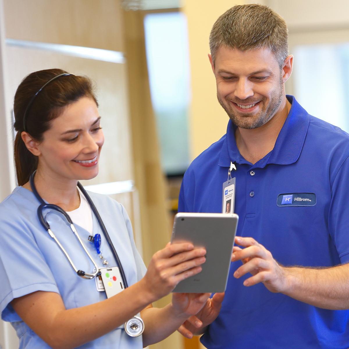 Infirmière et technicien de Hillrom qui discutent avec une tablette dans les mains