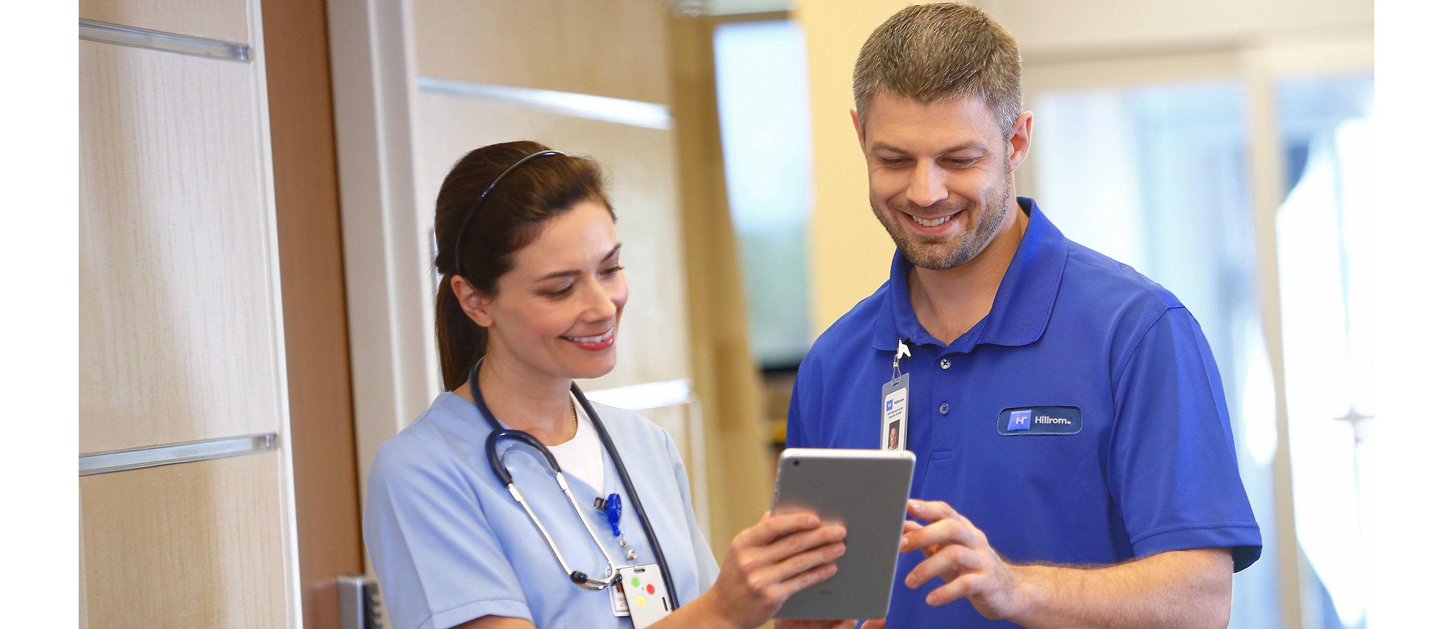 A Hillrom support representative looks at a tablet with a clinician in a hospital corridor