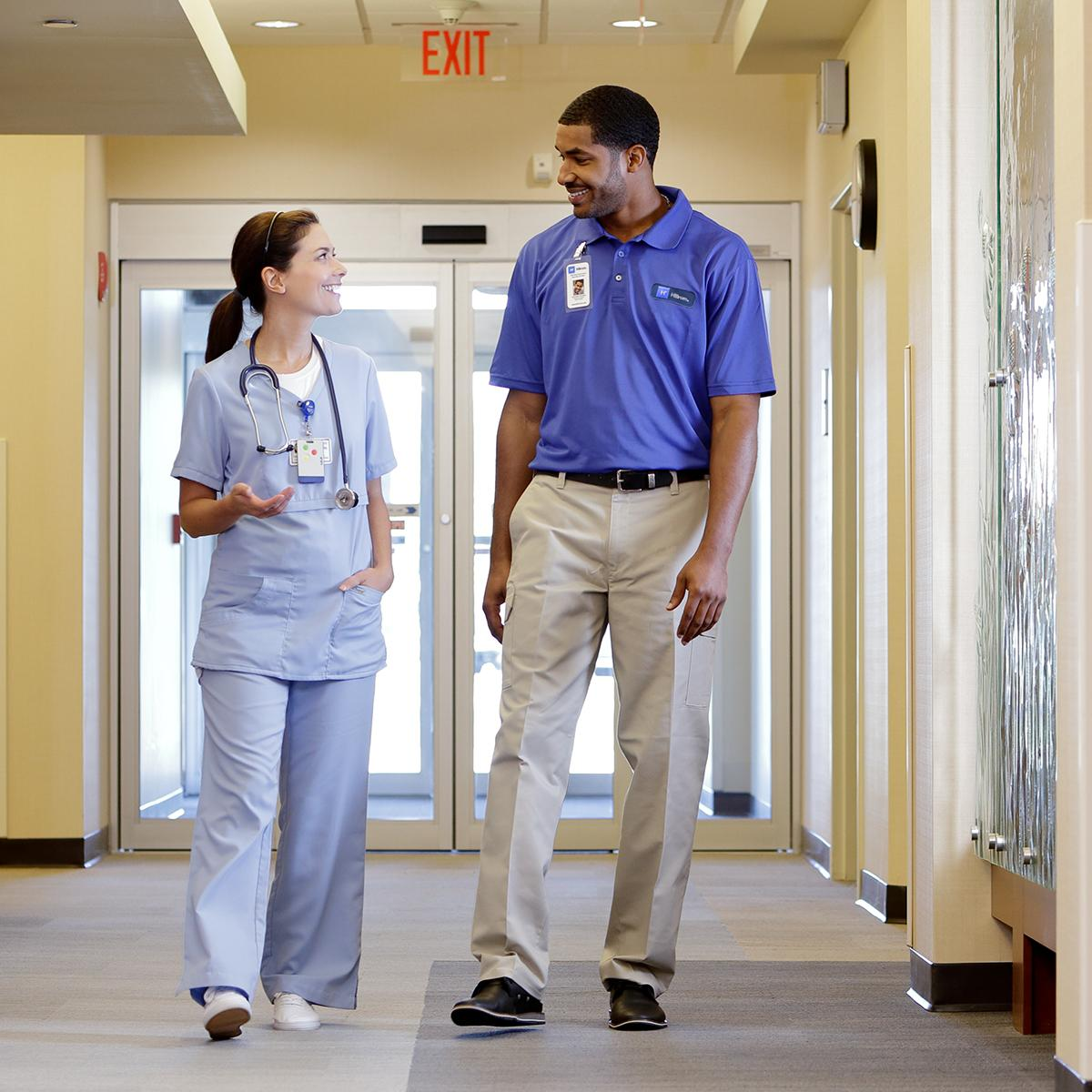 A clinician and a Hillrom support professional chat as they walk in a healthcare facility corridor.