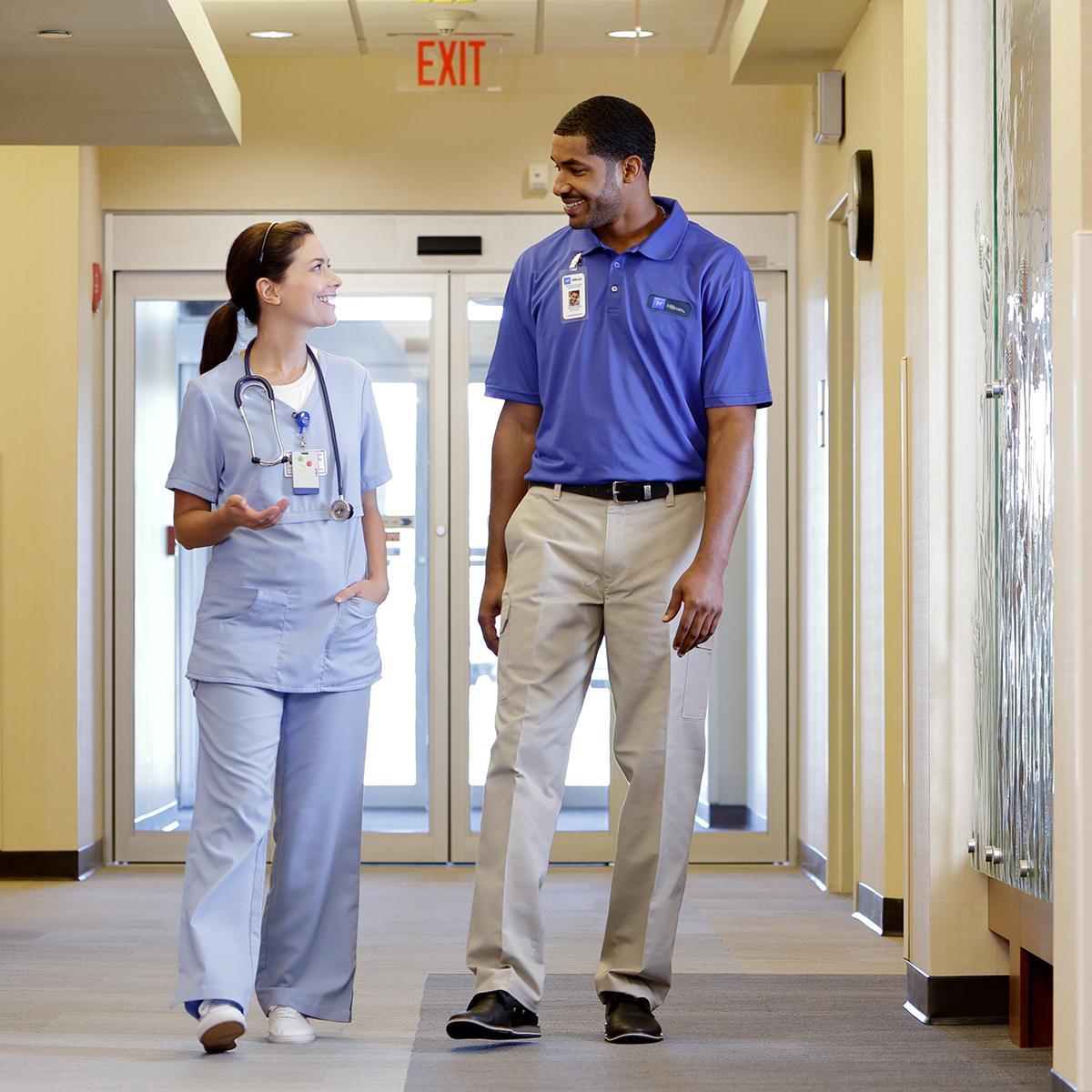 Infirmière et technicien de Hillrom qui discutent dans un couloir d'hôpital