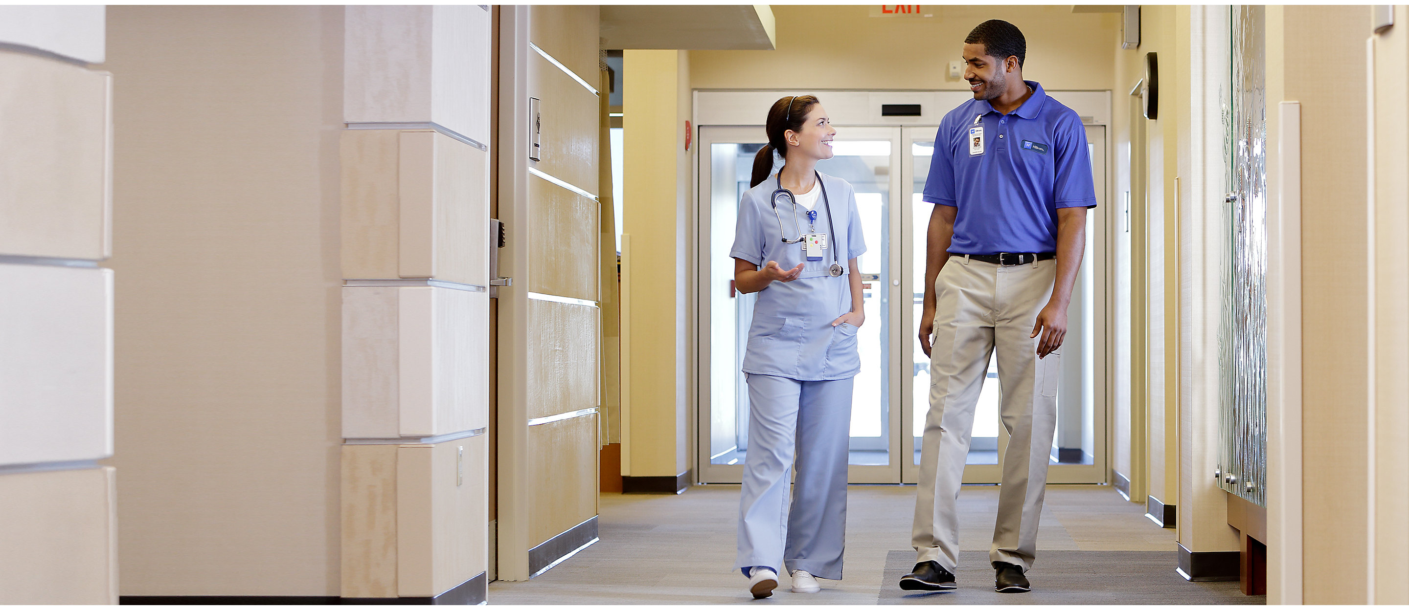 A Hillrom instructor walks down a hospital hallway, talking with a clinician