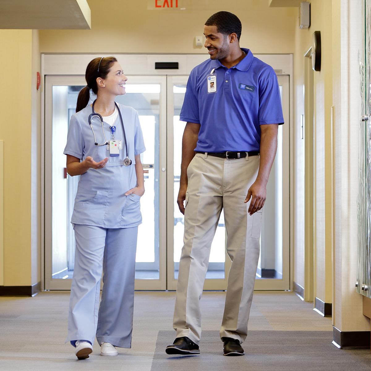 Nurse and Hillrom technician interacting in a hospital hallway