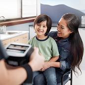 Système de dépistage visuel Spot® tenu par un clinicien (partiellement vu en premier plan), et le jeune patient et sa mère, assis, dans le plan intermédiaire