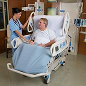 A patient sitting in the TotalCare SpO2RT 2 ICU Bed is comforted by his clinician