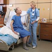 An older male patient sits up on the VersaCare Med Surg Bed. A female clinician stands at the bedside, assisting him with her hand on his shoulder.