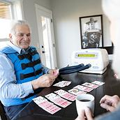 An older man uses The Vest System while playing solitaire at his dining room table.