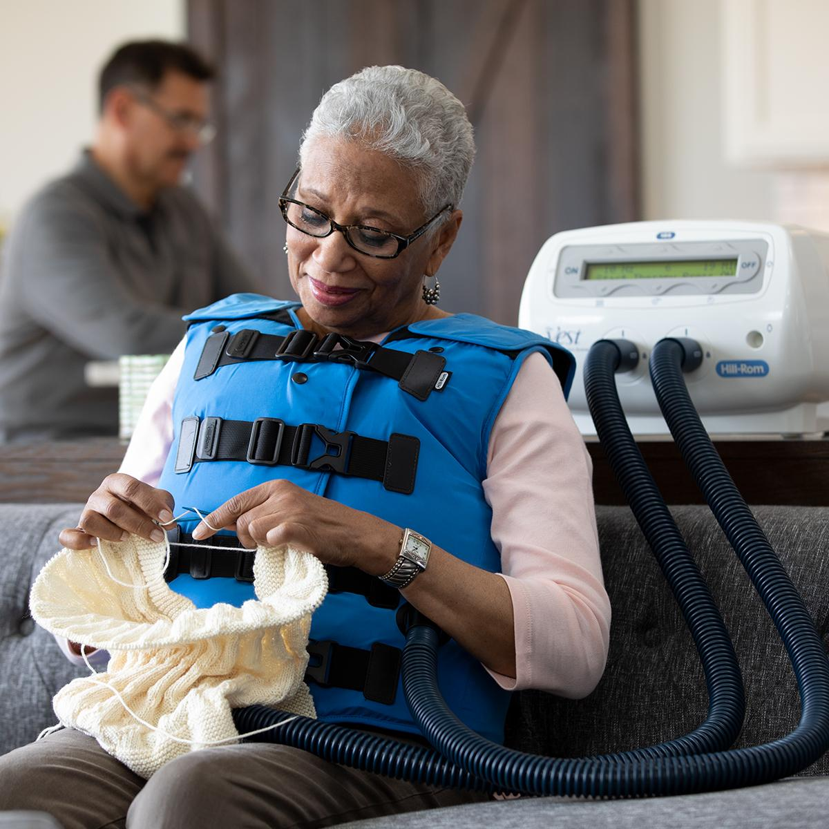 An older woman knits in her living room while using The Vest System with a Coastal Blue vest.