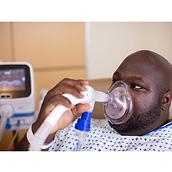 A patient receives OLE respiratory therapy from a Hillrom Volara System through a facemask interface.