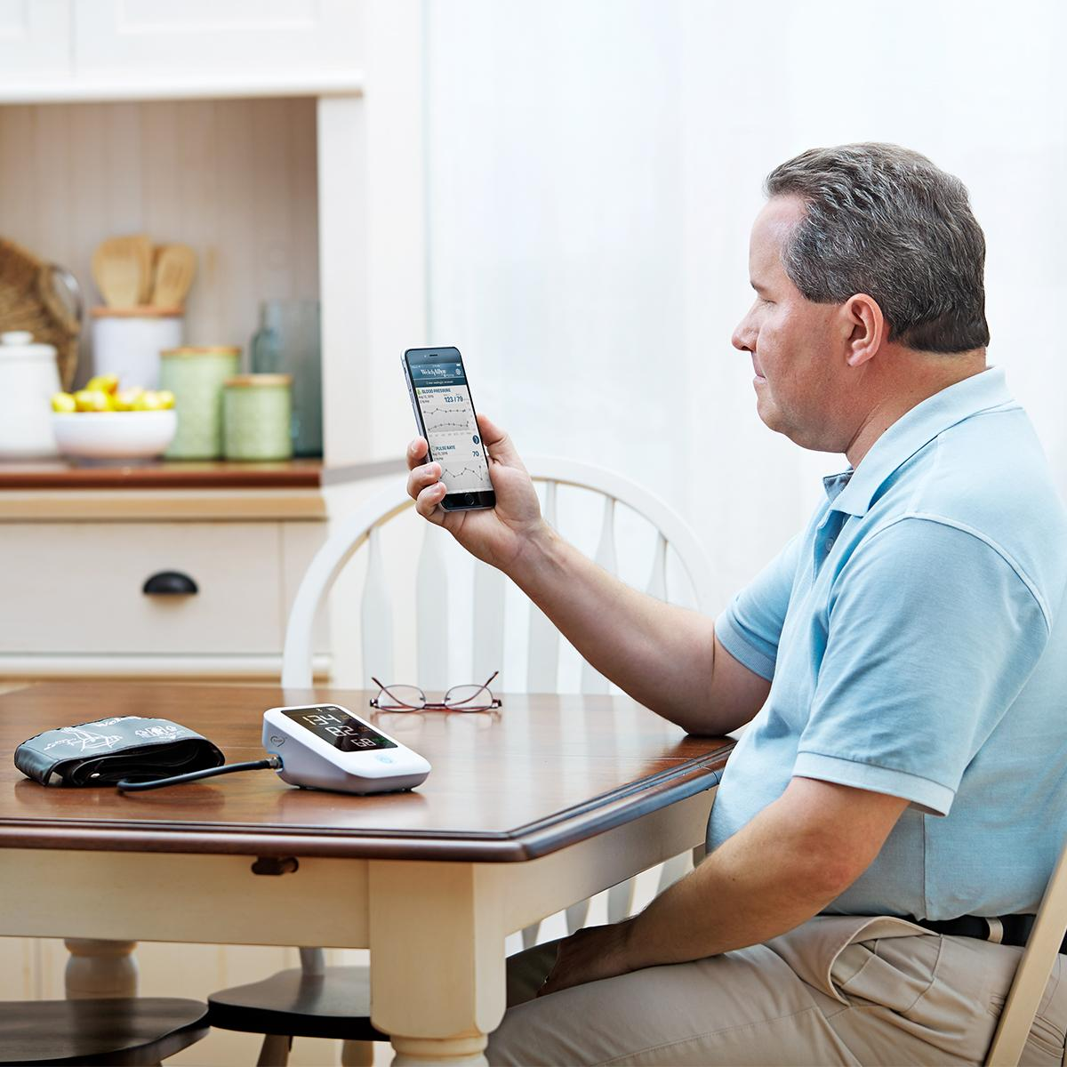 Patient looking at phone while sitting at table with Welch Allyn Home Blood Pressure Monitor