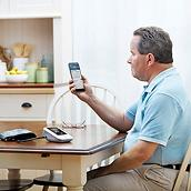 Patient sitting at table, using Welch Allyn Home Hypertension Program on smartphone