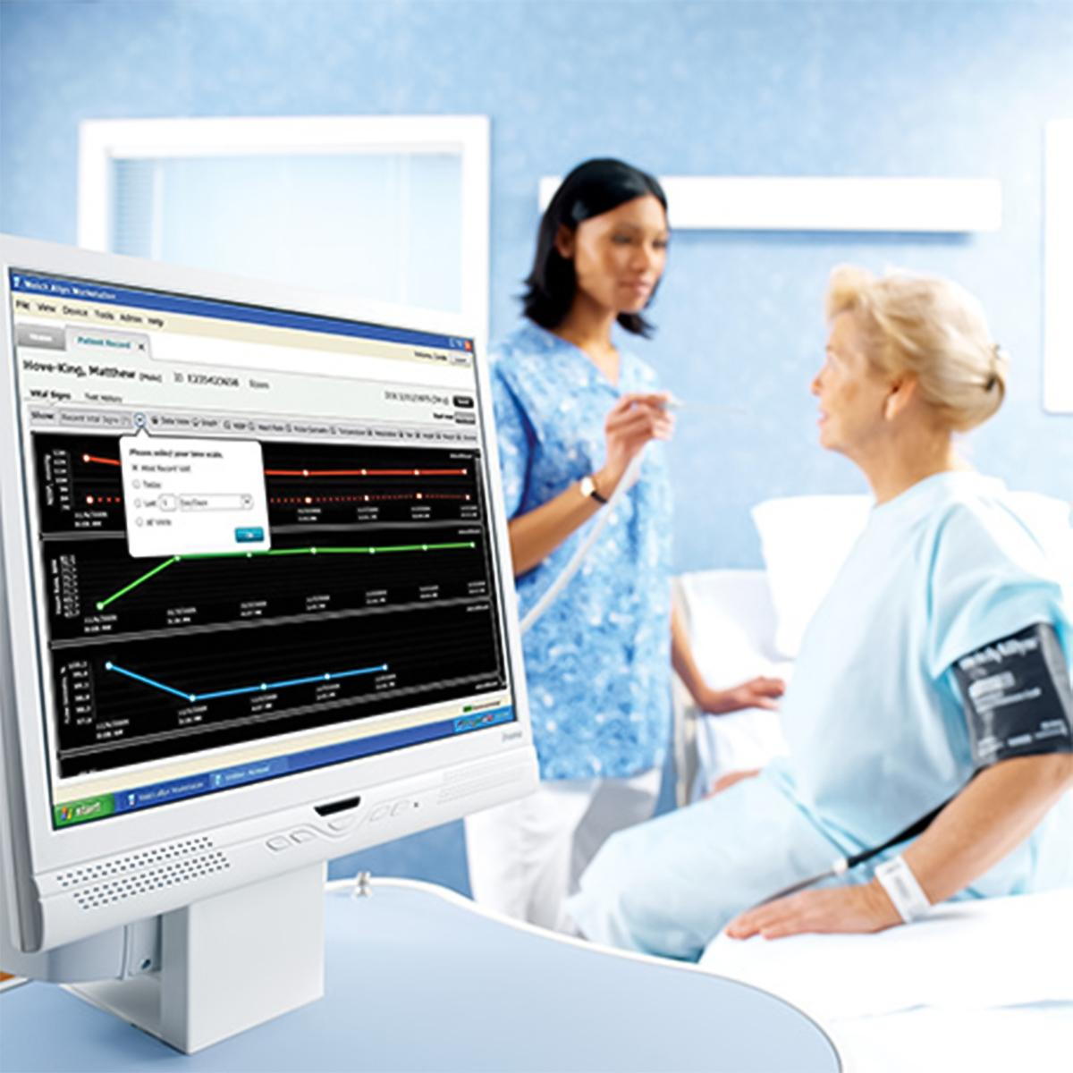 Clinician talking to patient in the background with Connex Vitals Management Software appearing on a desktop computer screen in the foreground