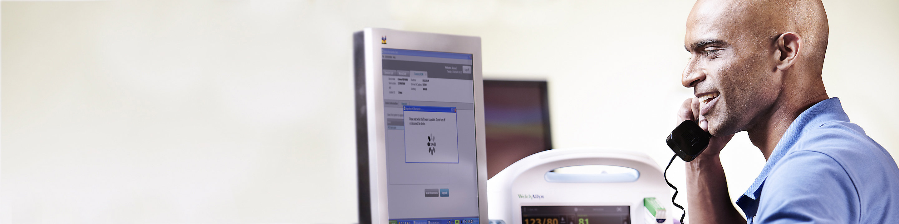 A biomedical engineer taps the Graphical Caregiver Interface (GCI) Touchscreen on a Centrella Smart+ Bed.