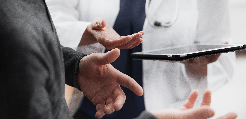 Una médica comparte información con su paciente en una tableta. Se muestran las manos en una conversación activa.