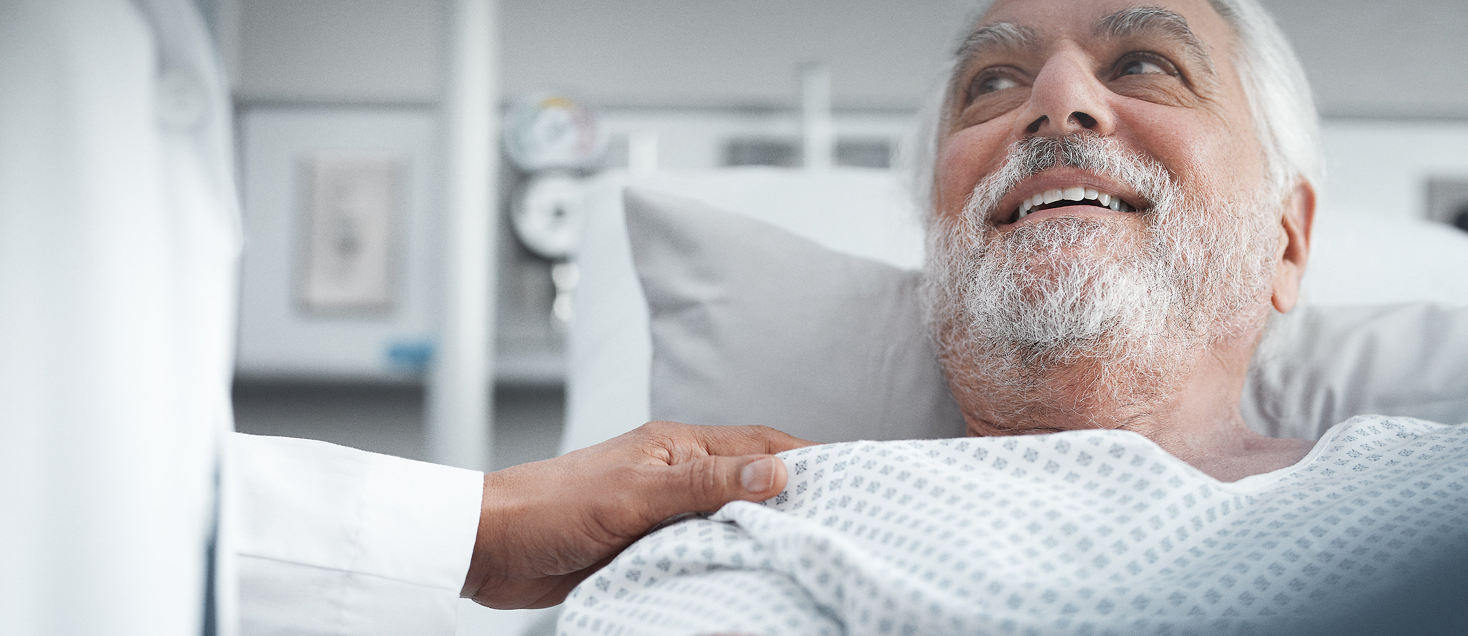A physician comforts and older male patient, lying in a hospital bed, placing a hand on his shoulder.