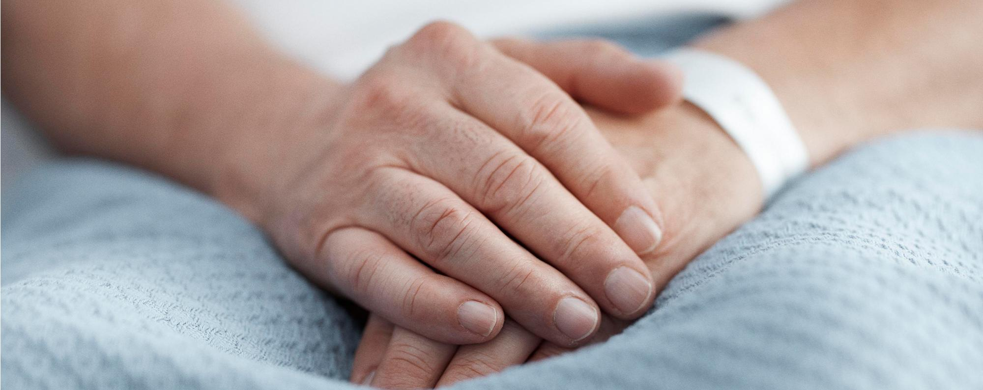 Hands folded on a patient's lap in an acute care setting