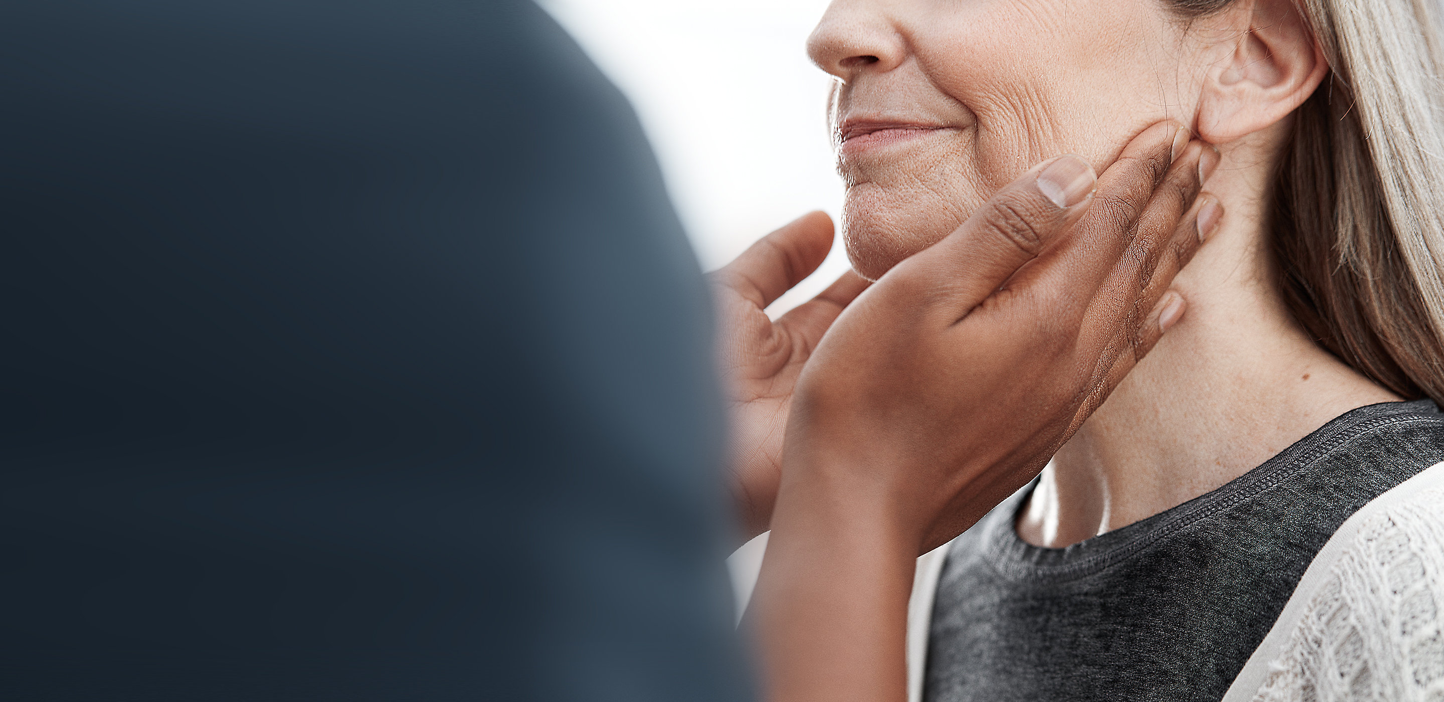 A clinician feels a patient's neck and throat lymph nodes during a physical exam