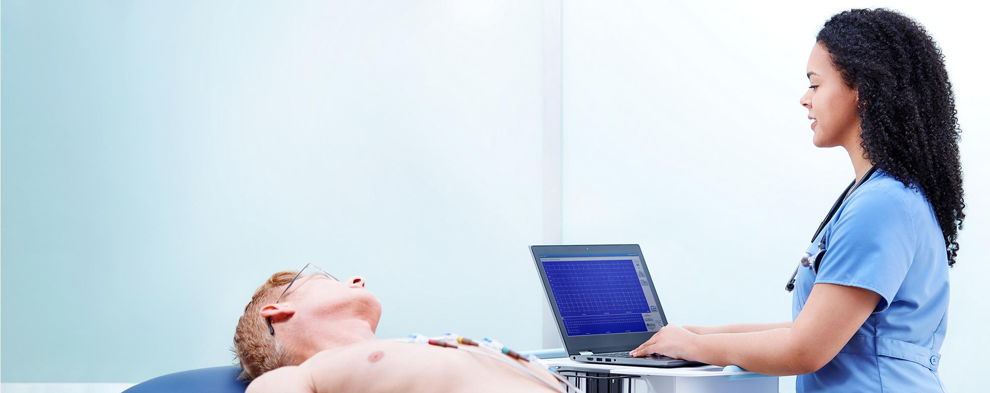 Patient connected to the Welch Allyn® Diagnostic Cardiology Suite™ ECG while a clinician looks at the results on a laptop.