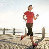 A smiling woman runs along a waterfront.