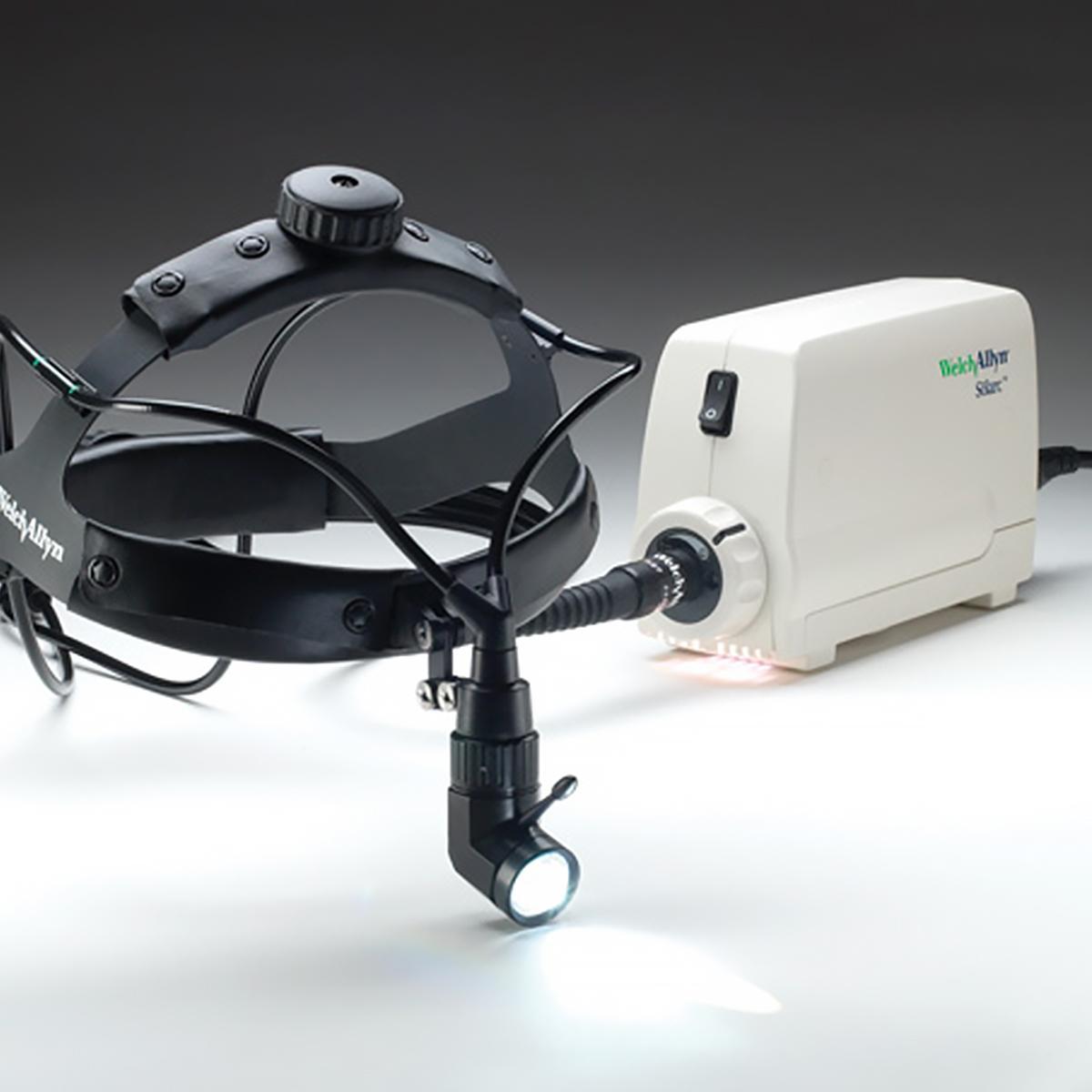 Lampe frontale chirurgicale WelchAllyn MFISolarc, branchée à sa base. La lampe est fixée à un serre-tête noir ajustable.