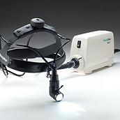 A Welch Allyn MFI Solarc Surgical Headlight, plugged into its base. The light is attached to a black, adjustable head strap.