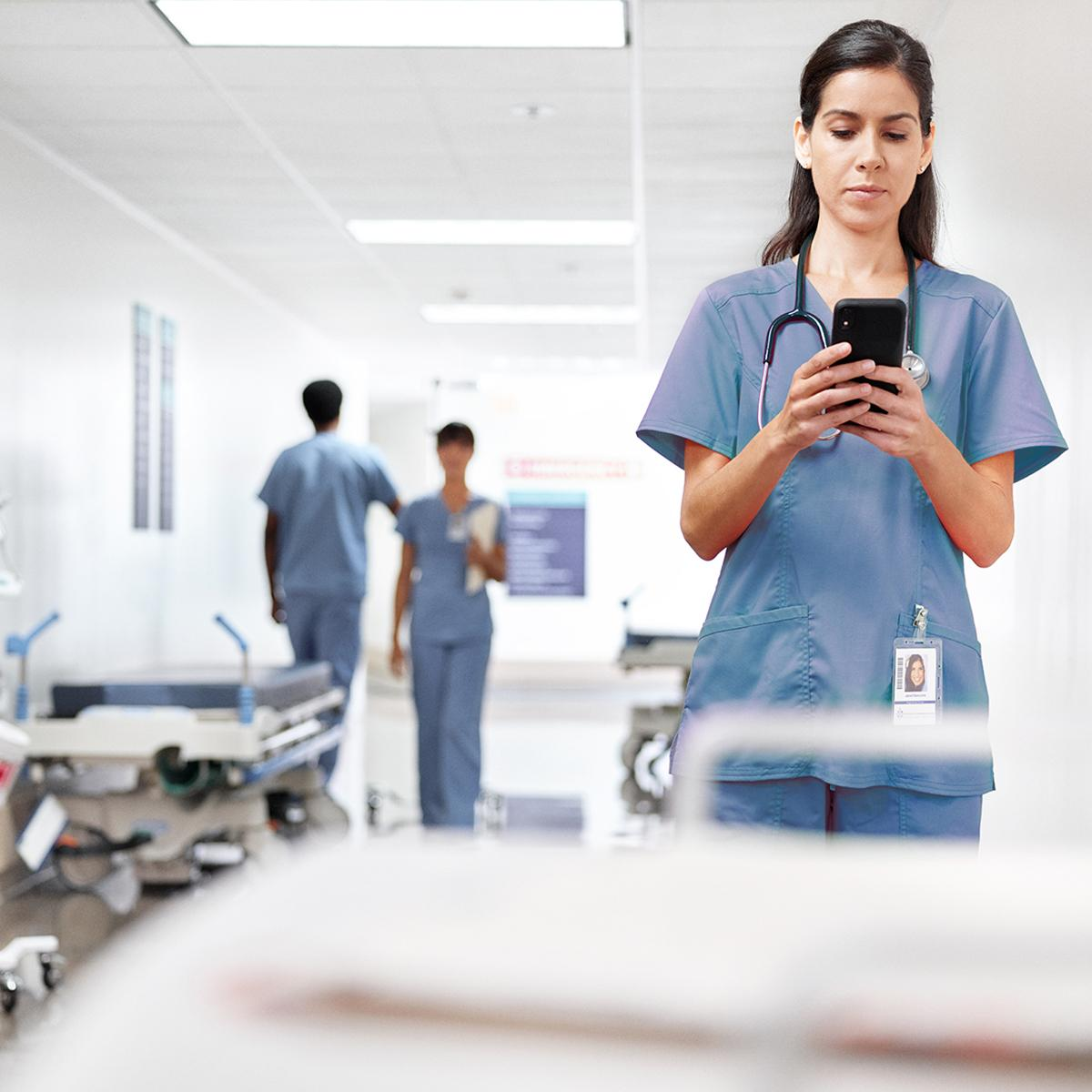 Nurse using smartphone in hospital hallway