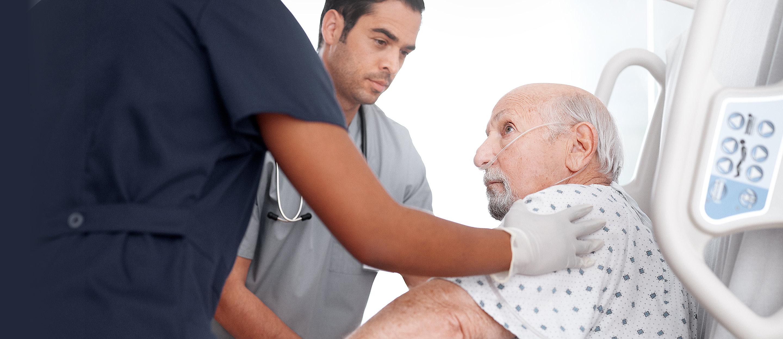 Cuidadores ayudan a un paciente a levantarse de una cama Progressa®.