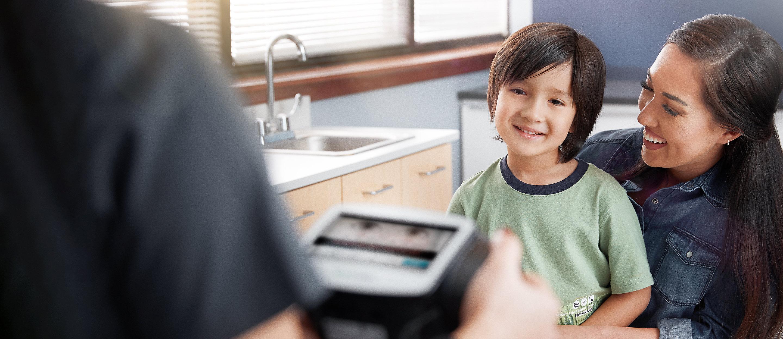 Un médico realiza un examen de la vista a un niño utilizando el Evaluador de visión Spot®.