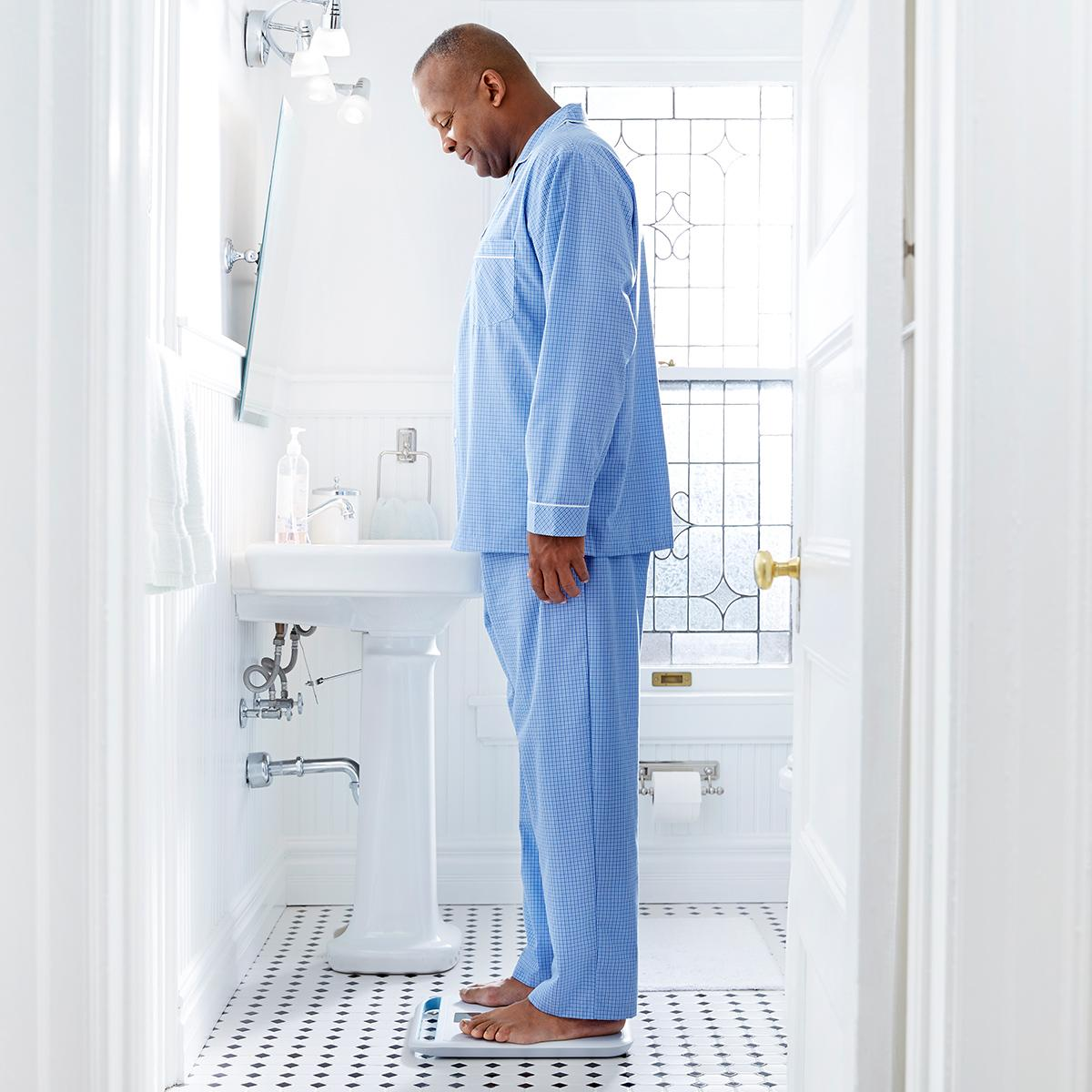 Patient standing on Welch Allyn Home Scale in bathroom