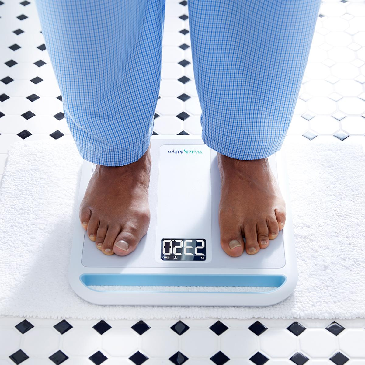 Close view of patient standing on Welch Allyn Home Scale