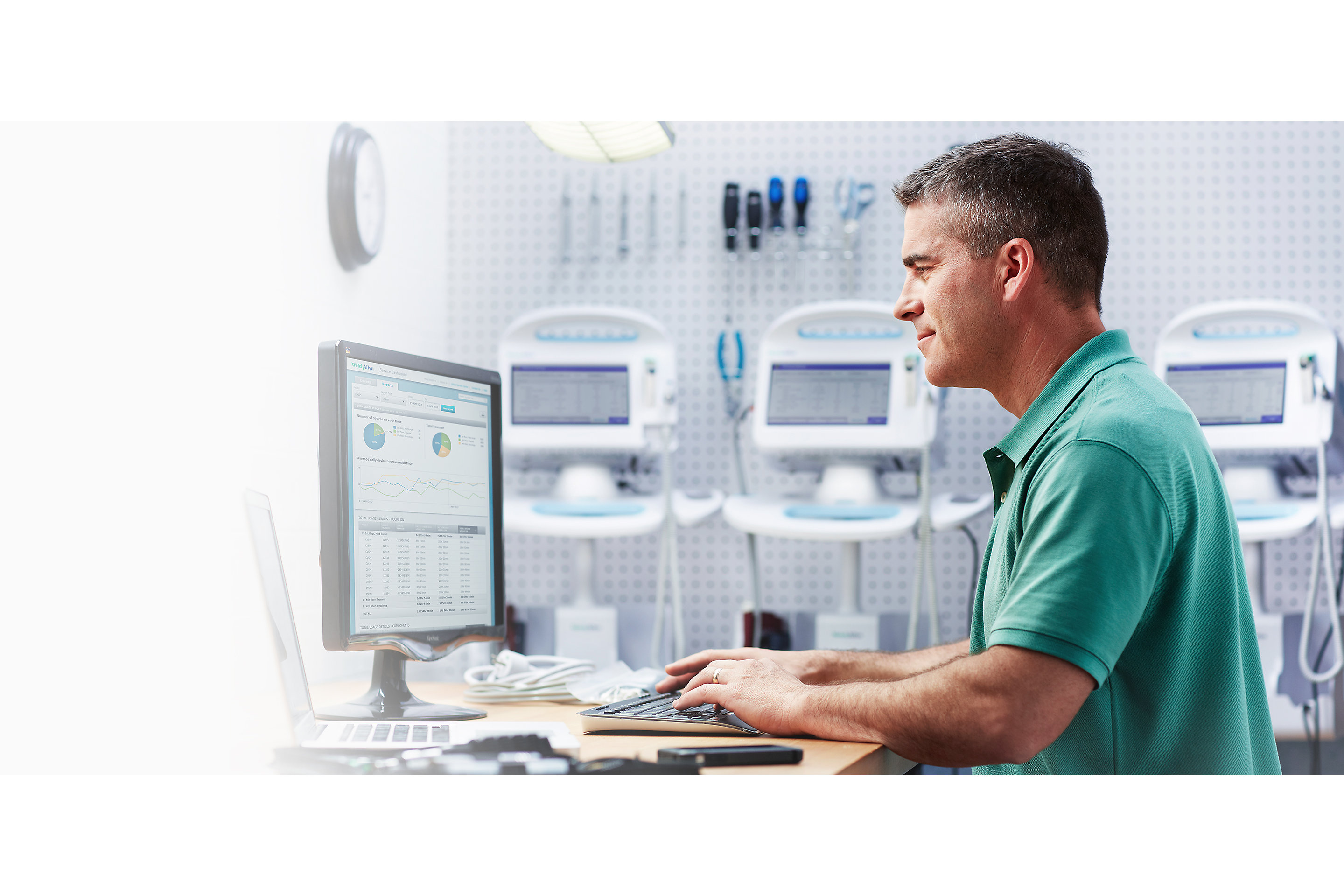 A biomed reads information on a computer screen. Tools and Connex® Vital Signs Monitors are in the background